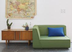 Canapé vert avec coussin bleu dans un intérieur à la déco vintage.