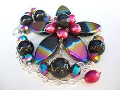 Black flower necklace, asymmetrical beaded wire wrapped flower with peacock purple gold green rainbow AB finish bead flower jewelry. $44.00, via Etsy.- see STARTJEWELS by Sarah Stettler- lots of unique items in her shop!