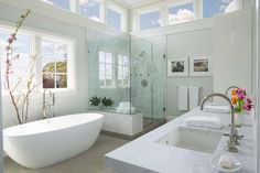 Luxurious master bathroom framed by clerestory windows is equipped with an oval freestanding bathtub placed in front of a cherry blossom branch, beneath a window framed by a pale gray wall, and beside a seamless glass shower fitted with a marble surround, marble bench, and a polished nickel shower kit.