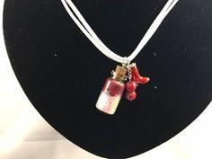 Leuke dubbele witte suede ketting met wensflesje in rood/wit. Daarnaast twee leuke bedels van een laars en twee rode balletjes. De ketting is 46 cm lang.