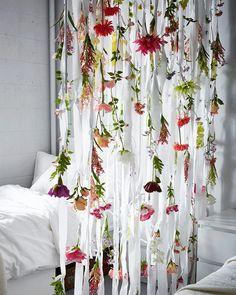 リボン状にカットしたホワイトのカーテンに取り付けたさまざまな造花。
