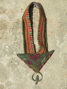 Kinship Stories: Tribal art necklace whose base is made of a vintage piece of applique, coming from a woman's belt from the Hmong tribe in the Hoa Binh province (Vietnam). The central triangular piece is an Afghani amulet, where people traditionally hid scriptures for protection. The sterling silver earring (925k) is Hmong and also comes from Vietnam. This necklace is entirely handmade and a one-of-a-kind piece.