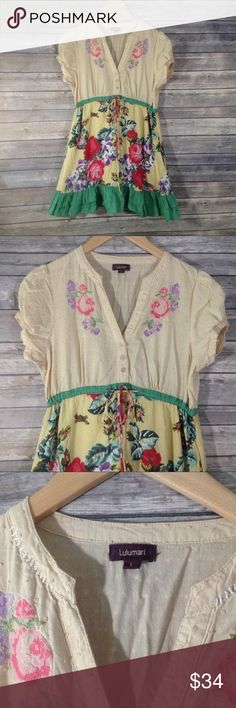 Lulumari Floral Embroidered Tunic/Dress This is so, super cute. This dress or tunic is by Lulumari and it is a Size Large. It features a textured Swiss dot fabric on the top with needlepoint style embroidery. There is a bow-tie drawstring waist. And the skirt portion features a print that looks like embroidery and cute ruffles! In good used condition. There are some hardly noticeable black dots on the front (see picture) and it appears to be a little faded. Lulumari Tops Tunics