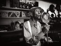 An elderly african-american man sings into a vintage microphone inside of a room full of antique radios