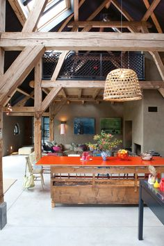 A #converted #barn #orange #table  #wood #living_room in the Netherlands