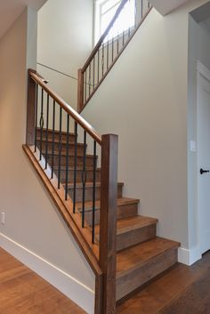 Wood stairs with decorative metal spindles.