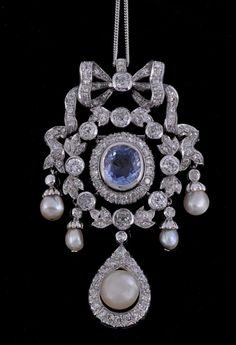 A sapphire, diamond and pearl pendant pendant/brooch, the central cushion shaped sapphire, estimated to weigh 3.44 carats, in a raised collet setting, within a surround of eight cut diamonds, to a decorative openwork surround and a ribbon bow surmount set throughout with old cut and eight cut diamonds and pearls, suspended below is a pearl within an eight cut diamond set pear shaped surround, on a fine curb link chain, the pendant 6.8cm long, chain 36cm long