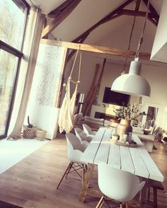 white table, chairs, lamp, and wood beams