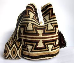 $90.00 CAYMAN MOCHILA. About Wayuu Mochilas: These crochet Wayuu bags are made by Wayuu women and designed by Lombia & Co. The colors of the mochilas Wayuu are inspired by the vivid colors that surround region of La Guajira. Sand, sea, desert, sun and a clear sky are constants in the landscape. Geometric figures are a signature of these mochila bags.