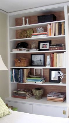 I've always loved this bookcase composition and shared it in a previous about creating a dazzling display. This white bookcase was dressed up with the addition of grasscloth wallpaper at the bookcase back.  It adds an unexpected touch to a typical built-in – via Cottage and Vine