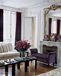 white couch + purple velvet settee + black coffee table + white fireplace + gold mirror + white crown molding + herringbone hardwood flooring