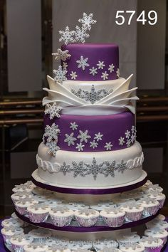 4 Tier white & Purple Wedding Cake with glittery snow flakes. Also cupcakes with glittery snow flakes