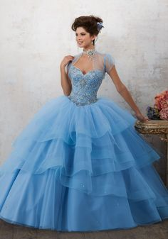 Morilee Quinceanera Dresses  STYLE NUMBER: 89130 Jeweled Beading on a Tiered Tulle Ballgown  This Dreamy Tulle Quinceañera Ballgown Features a Gorgeous Gemstone Beaded Bodice with Corset Back. The Tiered Skirt is Accented with Delicate Scattered Beading and Horsehair Trim. Matching Bolero Jacket included. Colors Available: Champagne, Ballet Pink, Bahama Blue, White.