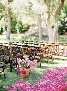 bougainvillea flower petals line the ceremony aisle