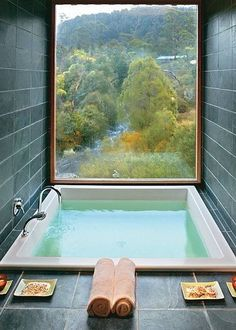 this spa in bathroom looks really relaxing and it has a big window which brings the natural light in and has a lovely view from outside