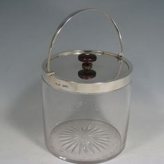 Antique Victorian sterling silver and hand-cut crystal biscuit jar, having a plain round crystal body with straight sides, star-cut base, plain rim with hinged swing-handle, and lift off lid with wooden finial. Made by John Grinsell of London in 1898. Height inc. handle 20 cms (8 inches), diameter of body 12.5 cms (5 inches).