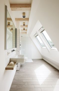 Unique take on a bathroom. Vaulted partial ceiling/wall with recessed vaulted windows. Subtle grey brown tile flooring, exposed ceiling beams, free standing sinks with wall mount faucet and a small extended wood counter. Standing shower in the background with white tiles, and I think full glass partitions. Beautiful!