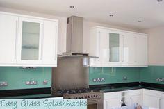 Mint Green coloured glass splashback in a White Kitchen with black worktop…