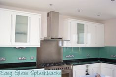 Mint Green coloured glass splashback in a White Kitchen with black worktop. Visit easyglasssplashbacks.co.uk to discover more.