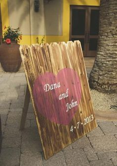 Wooden fence look wedding sign with names in heart.