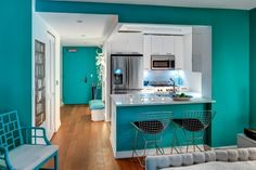 petite cuisine élégante avec peinture turquoise, armoires blanches et appareils encastrables