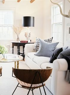 Fresh and bright white living room with blue pillows, glass coffee table, and black table lamp