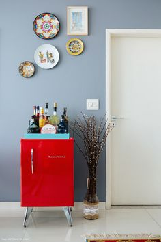 Parede cinza, pratos decorativos e frigobar retrô vermelho nessa sala de jantar.