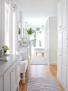 Large armoires take the place of walk-in closets in this master suite. Windows between the two vanities and behind the claw-foot bathtub bring ample light into the narrow space.