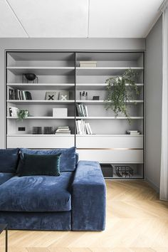 AKTA designed a refined and decorative interior. Monochrome background enhances rich colours and allows the artworks to stand out. Cold grey tones are balanced by velvet fabrics which also make a contrast to the textured ceiling. #bookshelf