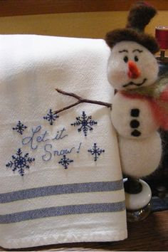 """Enjoy a FREE embroidery design featuring beautiful snowflakes falling around """"Let it Snow!"""" all in chilly blue #8 Perle Cotton.  Just print out the pattern and transfer the design to a Navy Striped Tea Towel.  Have fun with 2 simple embroidery stitches....fun and easy too."""