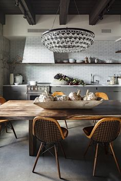 A little drama with a crystal chandelier takes the the kitchen table up a notch or two. #subway tiles #black beams #wood table.