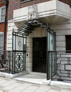 Art Deco Doorway:  It was built in 1932–3 to designs by E. B. Musman, with an iron and glass enclosed porch of 1936 by W. Turner Lord. London