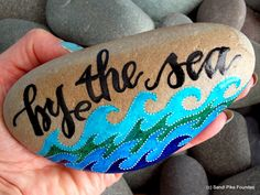 by the sea, by the sea, by the beautiful sea...  beach home decor. shades of blue. ocean waves. the call of the sea.  a perfect reminder of times by the ocean.  hand painted rock (sea stone) from Cape Cod.  A beautiful, taupe-gray stone, worn smooth over time being tumbled in the sea.  The colors on this sea stone are indigo, cerulean blue, teal, turquoise and white in layers of water resistant glaze inks over paint. Lettering is in black.  This stone has a calming, grounding weight when…