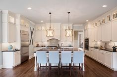 Gorgeous White Open Kitchen with Stunning Lighting and a Pop of Blue – Madison Model, Lake Haven of Crabapple – via Edward Andrews Homes