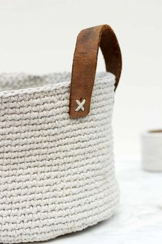 """Inexpensive utilitarian twine (from Dollar Tree!) and a thrifted leather belt combine to create a primitive, yet sophisticated home decor piece. This free crochet basket pattern is exceptionally easy to make with only single crochet stitches and can be customized to any size."""