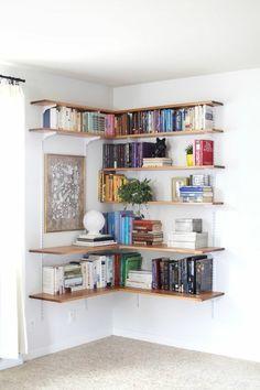 bibliothèque étagère en bois clair, moquette beige et murs blancs