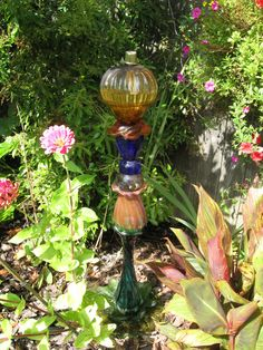 Glass garden tower made from stacked and glued thrift store glassware ~ great re-purposing project