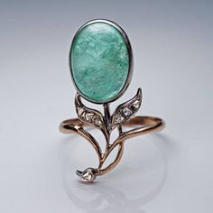 Made in Moscow between 1899 and 1904. A silver-topped 14K gold ring is designed as a stylized flower in Art Nouveau taste. The flower is set with a big cabochon cut emerald accented with old rose cut diamonds. The emerald measures 14 x 10.6 x 7.1 mm and is approximately 7.88 ct. The