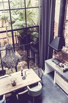 Converted warehouse home in Amsterdam. That black clay chandelier! That enclosed patio!  Image Via: Dustjacket Attic