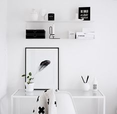 Minimalistisen valkoisen työpisteen äärellä esiin nousevat mustat yksityiskohdat. Ihana kompakti kokonaisuus. Pöydän lasilevy keventää ilmettä entisestään.