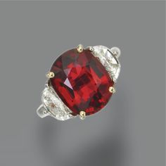 RED SPINEL AND DIAMOND RING The cushion-shaped red spinel weighing approximately 6.40 carats, flanked by 2 half-moon-shaped diamonds weighing approximately 1.55 carats, mounted in platinum and 18 karat gold