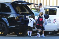 David Beckham loads up the back of their blacked out Range Rover after hitting the soccer field with his two youngest boys.