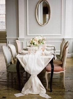 Fabric and lace table runner draped over table and tied with lace, ribbon, or twine along the sides