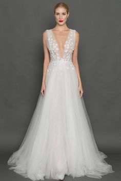 Modern A-line floor-length wedding gown with a deep v-neckline that is enhanced with hand embroidered butterfly appliques made from silk and metallic threads at the waist.