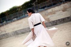 Fashion stylist Tina Leung flying around on a street style photo taken at Jardin des Tuileries during paris fashion week