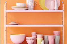 """""""Wow, diese Farbkombi ist ein Hingucker in der Küche: An einer Wand in Orange bietet das offene Regal in Rosa eine perfekte Bühne für Porzellan in ebenso zarten Rosatönen. Damit es nicht eintönig wird, stellen Sie noch welches in Hellgrau, Weiß und Gelb dazu - dann wirkt es lebendig."""""""