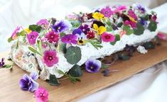 Rolled sandwich cake with cold smoked salmon, fresh cheese, herbs and edible flowers. http://kulinaari.blogspot.fi/2016/05/voileipakakku-kuin-kevaan-kuningatar.html
