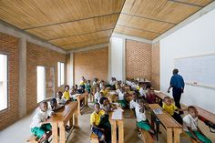 Umubano Primary School / MASS Design Group - double roofing with straw in steel frames and spaces between bricks creates air circulation and transparency
