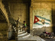 Fidel - the entrance to La Guarida restaurant - woman climbs the stairs that lead to the famous La Guarida restaurant in Havana Cuba