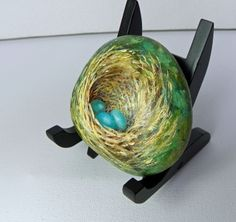 Side view of a Robins BIRD NEST Painted with acrylic on a natural river rock.